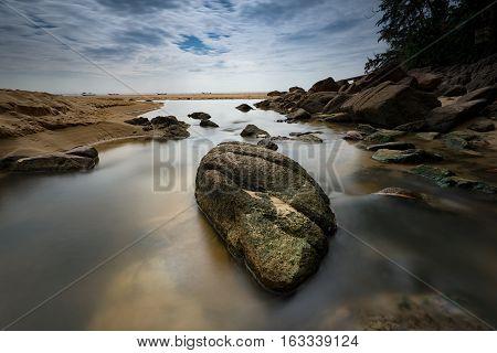 Long exposure water flowing on rocks .