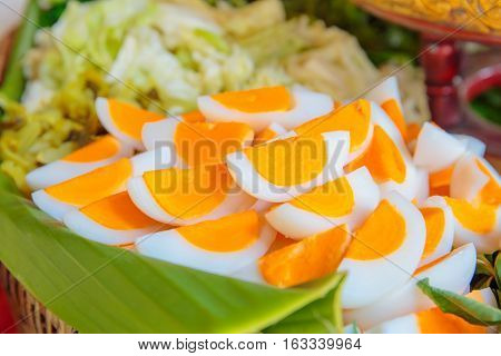 many of cut of boiled eggs with vegetable on the background.