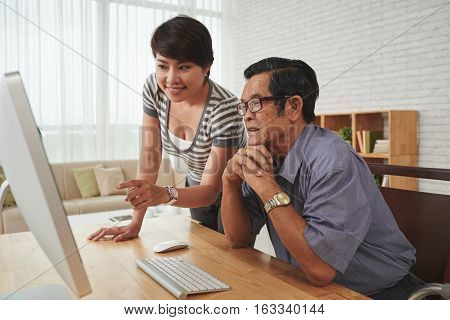 Young Asian woman and senior man watching something on computer screen