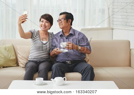 Pretty Asian girl taking selfie with grandfather