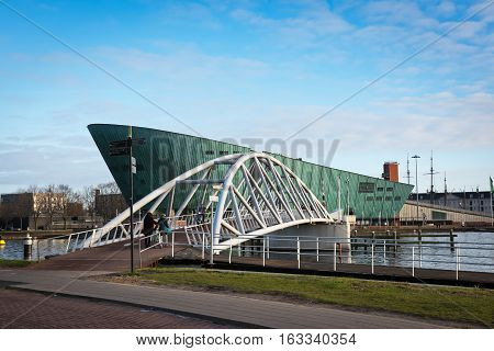 AMSTERDAM, NORTH HOLLAND/THE NETHERLANDS-DECEMBER 3,2016: Green building of NEMO Science Museum and white bridge leading to it. This museum is the fifth most visited museum in the Netherlands.