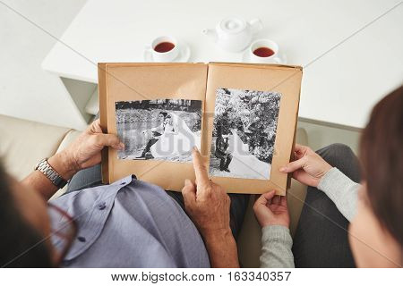 Senior man showing old wedding photos to his granddaughter