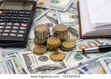 us coin on top dollar bills with pen and calculator.