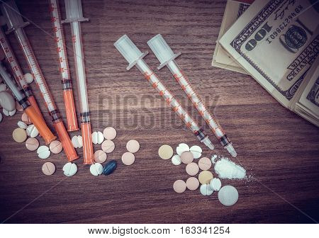 Injection syringe with cocaine pile and pills and dollar money.