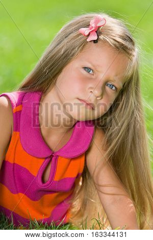 Serious Little Girl On The Green Grass