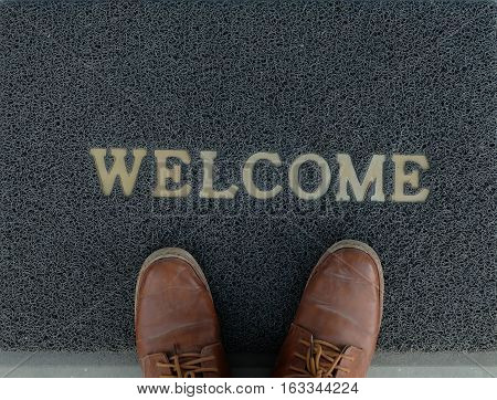 Welcome mat with your feet on it, doormat before entering the house.