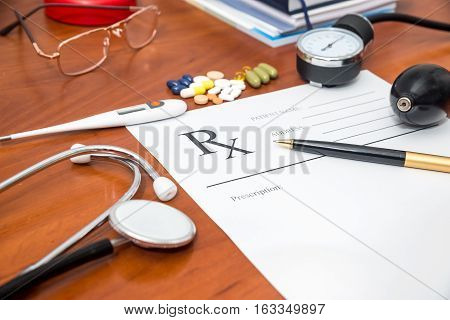 Blank medical prescription with stethoscope pills pen on desk