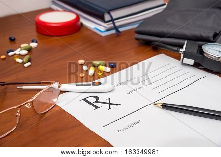 Blank prescription form with pills pen glasses and stethoscope