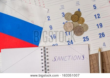 text russia sanctions on notepad with flag and money