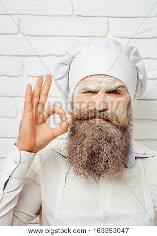 Handsome angry man cook or baker with flour on face beard and moustache poses in chef uniform and hat on white brick wall with ok gesture