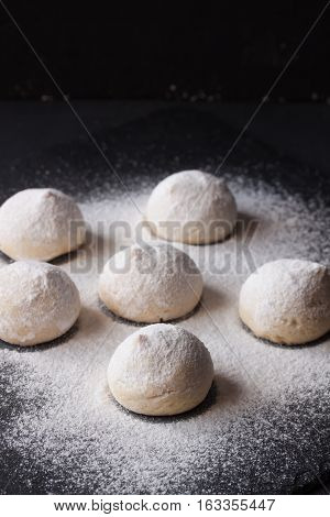 cookies with powdered sugar on a black background