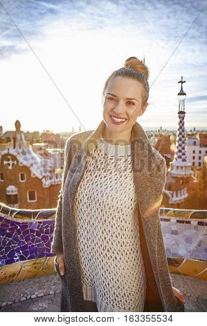 Smiling Trendy Woman In Coat At Guell Park In Barcelona, Spain
