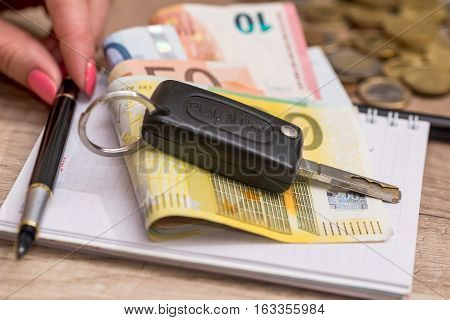 car key, note, pen and  euro on desk