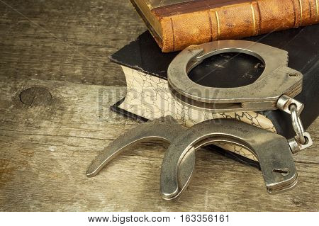 Book and handcuffs on a wooden table. The concept of punishment and justice. Punishment for a crime. Corruption and punishment. Arrest criminals. poster
