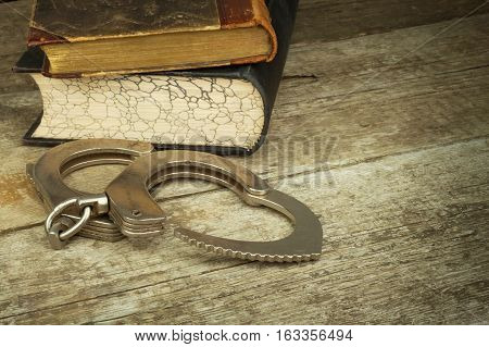 Book and handcuffs on a wooden table. The concept of punishment and justice. Punishment for a crime. Corruption and punishment. Arrest criminals.