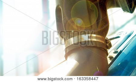 Straining clamps ventilation of a exhaust pipe poly plastic material Photography lens flare and building blur background.