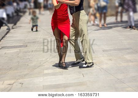 Street dancers performing tango in the street among the people