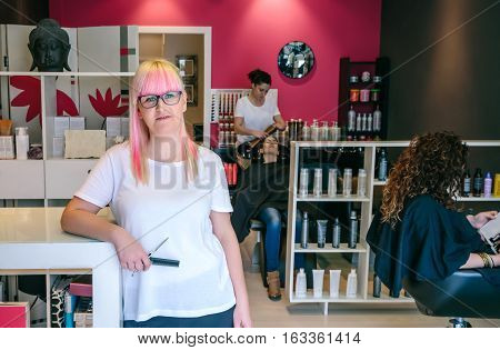 Woman hairdresser standing in a hair and beauty salon with customers in the background