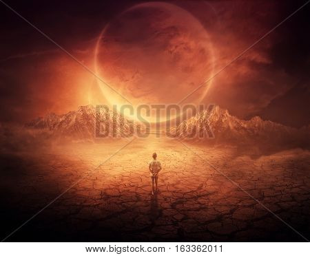Surreal background as a young boy walks on another planet with dry and cracked ground following a shining space object in the sky.