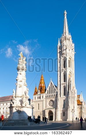 Roman Catholic Matthias Church and Holy Trinity plaque column at Fisherman's Bastion in Buda Castle District, Budapest, Hungary, Europe. Sunny day shot with clear blue sky.