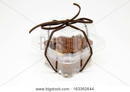 Pile of brownies in transparent plastic box for gift or present isolated on white.
