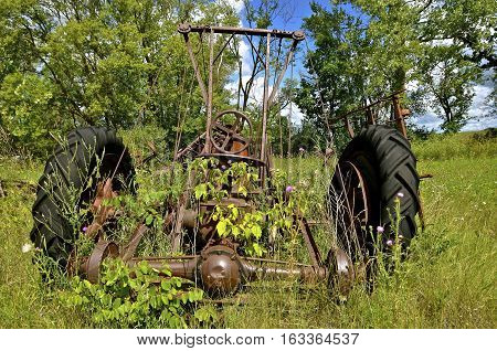 A front end loader apparatus was designed for the old tractor left in a junkyard