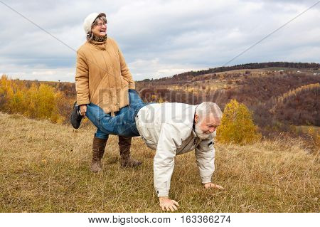 Elderly couple having fun and playing the wheelbarrow in nature.