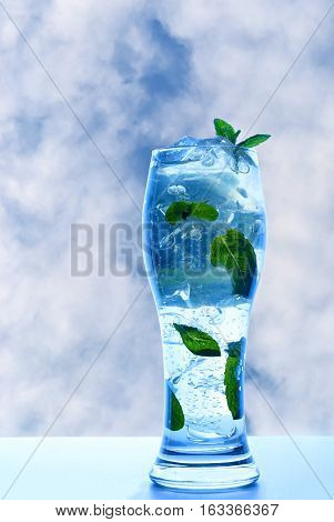 Minty refreshing drink in glass with ice and leaves on a background of blue summer sky and clouds