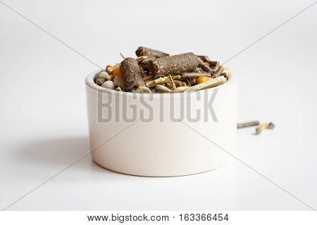 dry food for rodents in bowl on white background close up