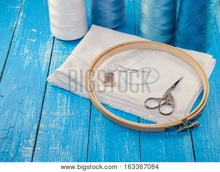 Threads in spools with white cloth for the embroidery and sewing blue gamma