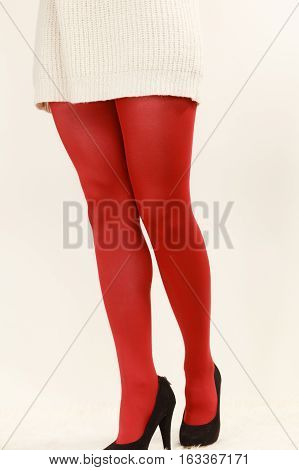 Elegant fashion outfit. Fashionable woman long legs in red vivid color pantyhose black high heels shoes on white