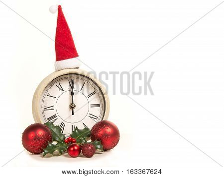 Clock standing on 12 o clock new year's eve with holiday decoration on a white background