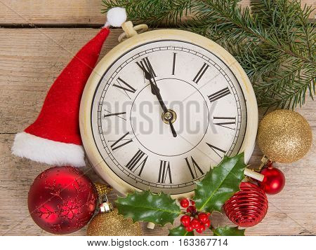 Close up of a clock on new year's eve with christmas decoration on a wooden background