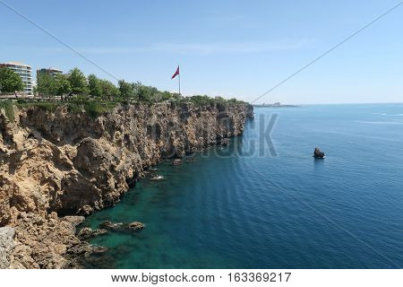 The Cliffs of Antalya, the Mediterranian Sea and a Small Boat in the Water