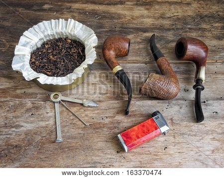 Wooden pipes, lighter, tobacco and pipe stopper on wooden table.