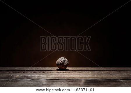 single walnut on a dark wooden background