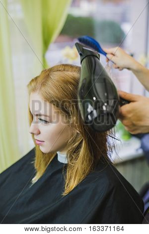 woman is making heir cut in salon drying hair