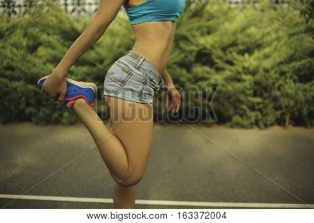 woman is stretching legs before the run