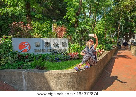 Young and smiling tourist takes a selfie at the entrance to the Hong Kong Park, the Supreme Ct Rd in Hong Kong Island, Central business district, China, Asia.