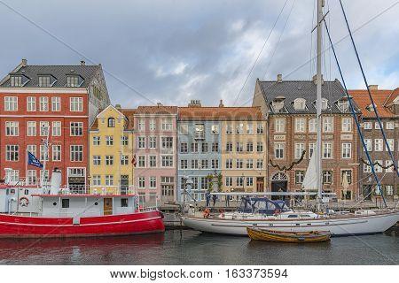 COPENHAGEN DENMARK - DECEMBER 24 2016: Nyhavn district is one of the most famous landmarks in Copenhagen Denmark and always packed with tourists.