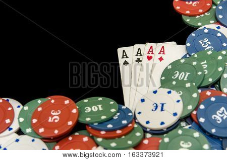 Four of aces and poker chips isolated on black background