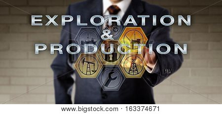 Torso of male corporate contractor in blue suit is pushing EXPLORATION & PRODUCTION on an interactive control monitor. Oil and gas industrial metaphor and communications technology concept for E & P.