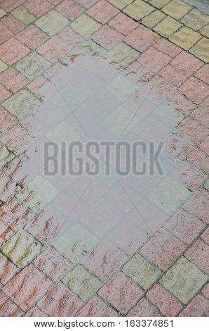 After rain in puddle.  Pavement texture. Background of old cobblestone pavement close-up.