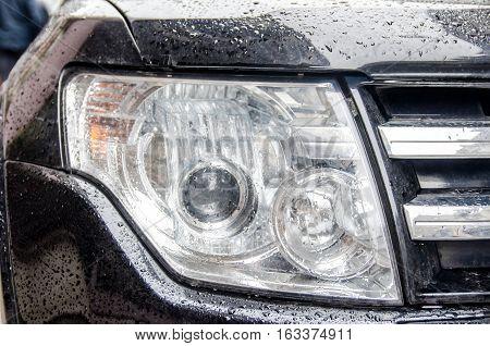 black Car headlights after rain close up
