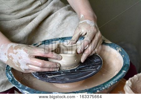 person potter makes clay earthen pot on a potter's wheel in pottery workshop