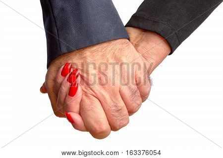 Elderly affectionate couple holding hands to show their lifelong love and commitment for Valentines day in a close up tender image isolated on white
