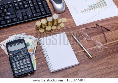 Business background view from above on a wooden table - empty notebook and pen dollar bills graph glasses calculator computer keyboard and mouse