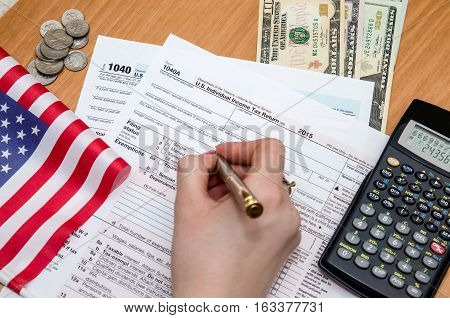 Business woman fills the tax form 1040 with money pen flag of USA and calculator