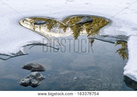 Reflection on frozen lake - hearrt shape on tarn Vrbicke pleso Slovakia