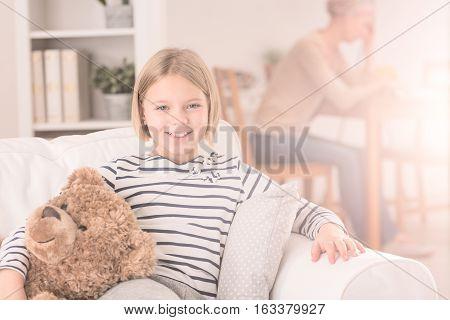 Happy Child Sitting On Sofa